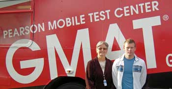 Pearson test administrator Ellen Mazurek, left, welcomes David Minnick, the 1,000th person to take the GMAT exam on the GMAT Mobile Test Center.